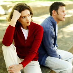 Couple sitting together looking tense