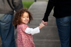 Little girl holding hands with parents